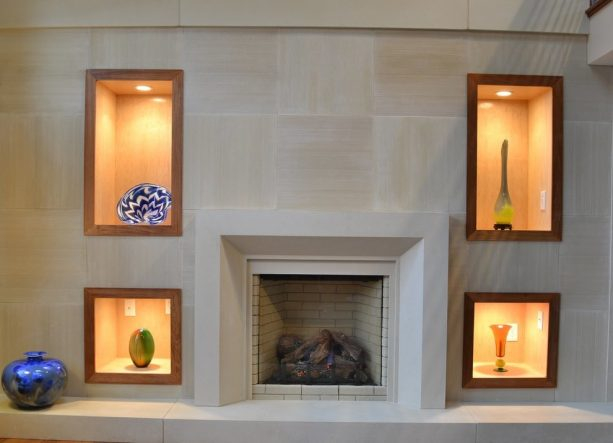 after makeover floor to ceiling tiles fireplace with built-in shelves with dramatic lighting, modern mantel and tiled raised hearth