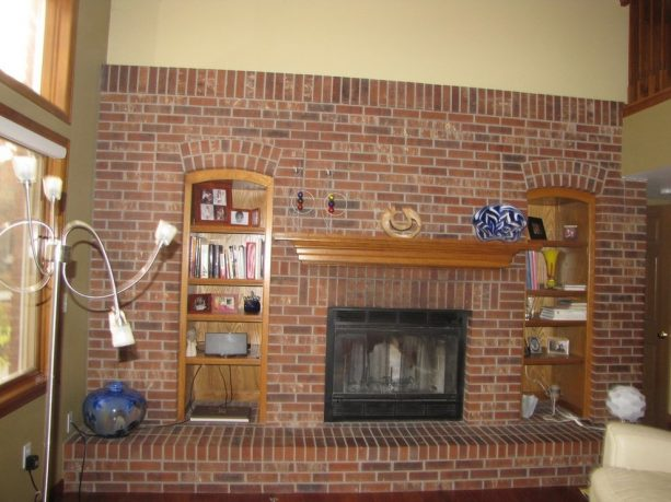 before makeover floor to ceiling brick fireplace with mantel shelf, built-in enclosing shelves and long raised hearth