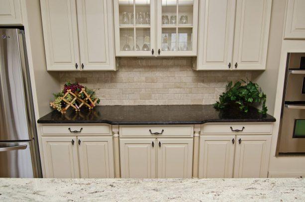 antique white cabinets with dark granite countertops