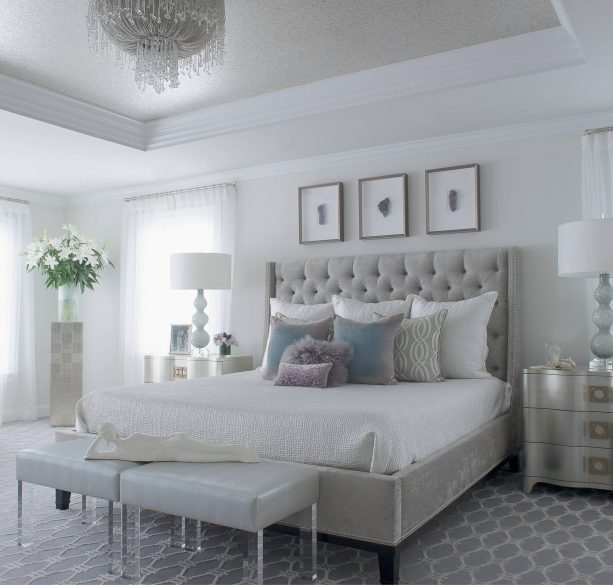 a bedroom with grey bed, white wall, and silver-colored furniture