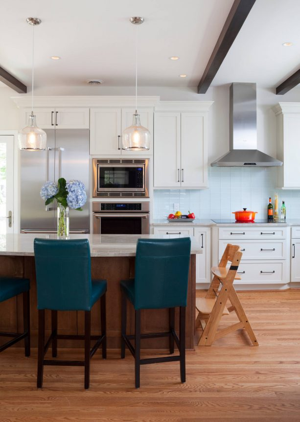 a kitchen with white cabinets and teal armless stools
