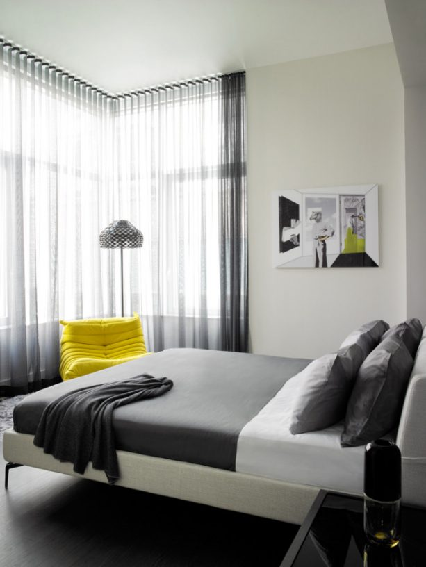 grey and white bedroom with accentuating lemon yellow chair