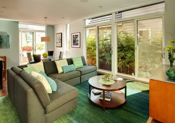 grey and teal living room with green accents and green view