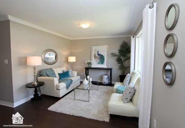grey and teal living room with peacock painting