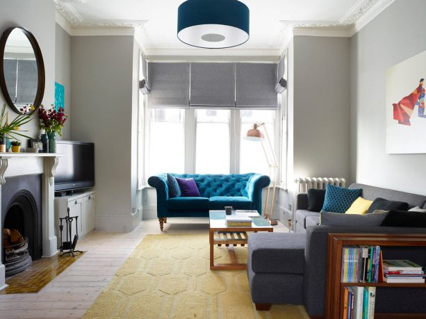 grey living room with teal tufted sofa