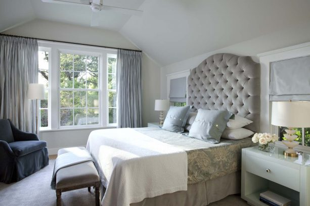 blue and grey bedroom with oversize tufted upholstered headboard