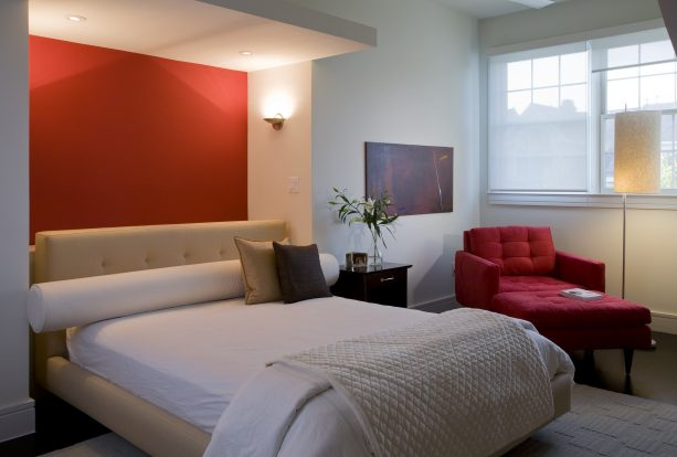 grey bedroom with small red accent wall