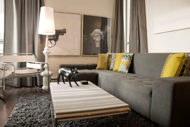 grey sectional couch with mustard cushions