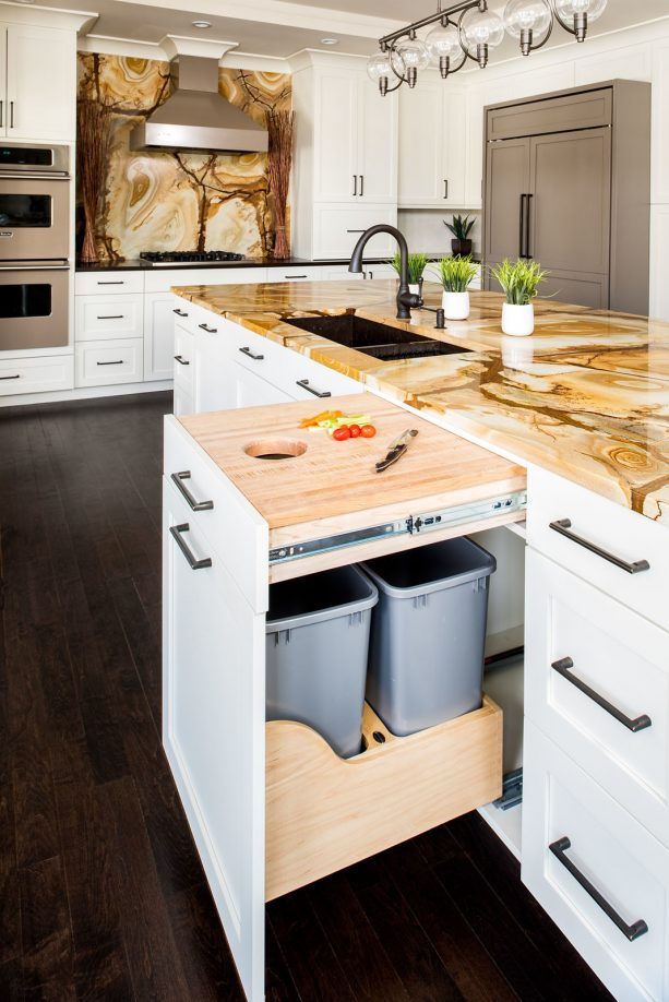 white shaker kitchen cabinets with integrated trash bins and cutting board