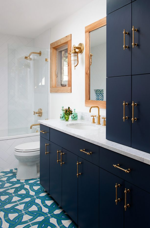 a bathroom with navy blue cabinets and brass hardware