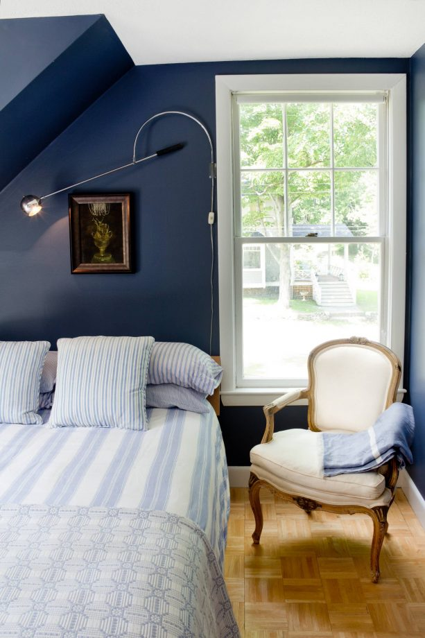 a bedroom with navy blue walls and soft blue bedding set