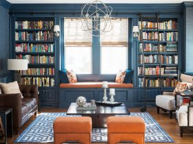 navy blue living room with orange ottomans and window seat