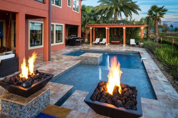 small inground pool with fire bowls features
