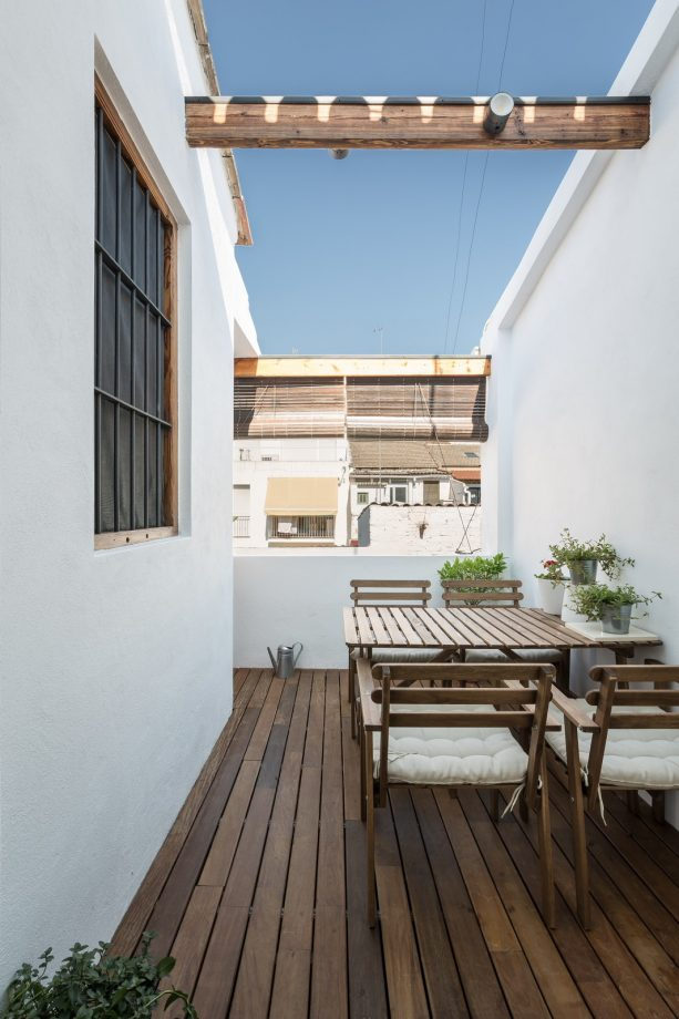 balcony with an outdoor dining table set and bamboo blinds