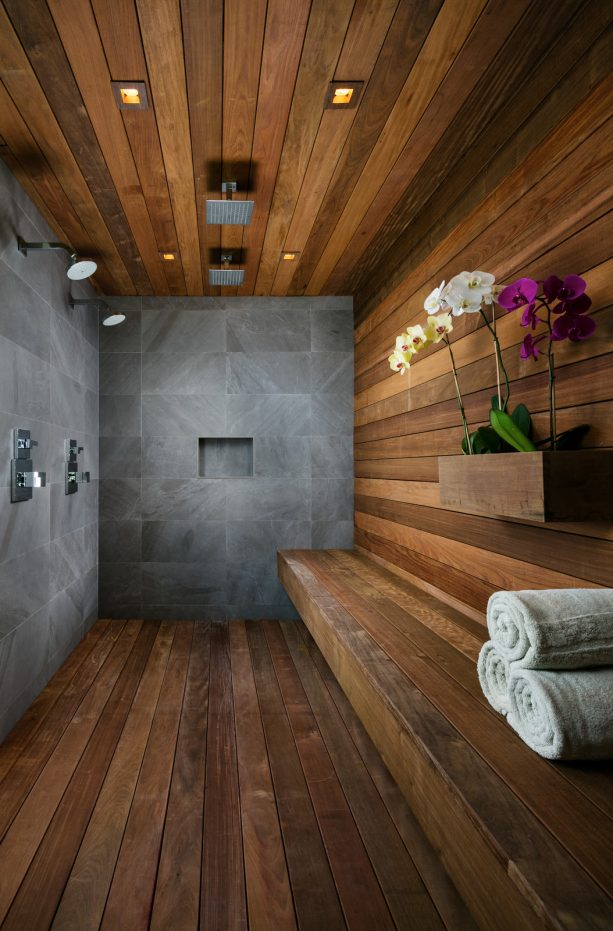 a spa-inspired bathroom that looks cozy with natural stone walls and dark hardwood floor