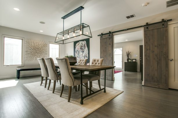 farmhouse dining room with light grey walls and stained red oak floor