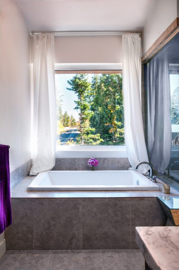 sheer white curtains for short wide window above a tub