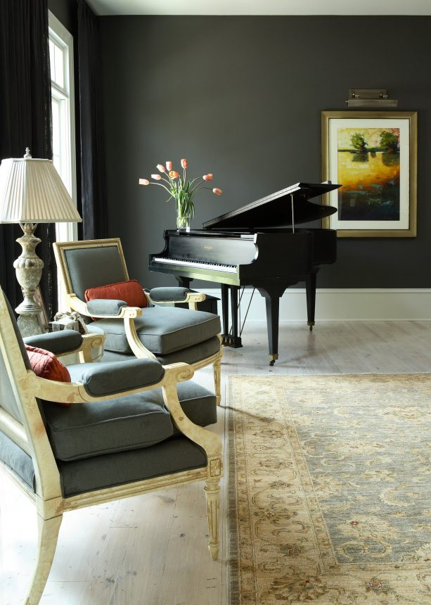traditional living room with charcoal grey walls and pine wood floor