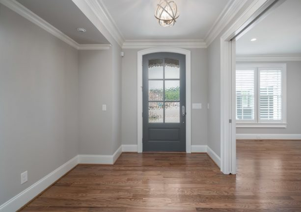 transitional entry with grey walls, hardwood floor, and darker grey door