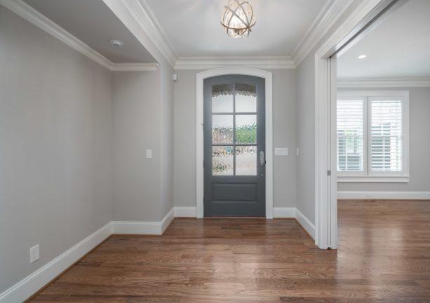 transitional entry with grey walls, hardwood floor, and darker grey door