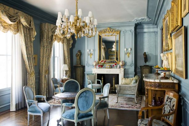 matte blue walls and patterned gold curtains in a traditional living room