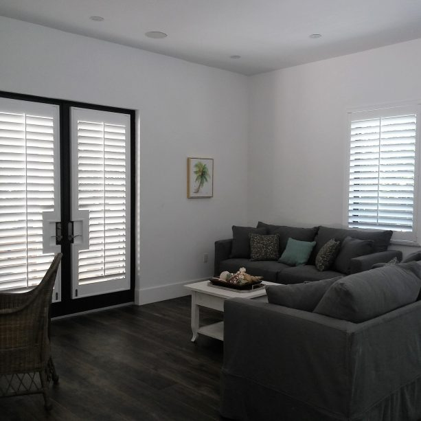 black French doors covered by white plantation shutters