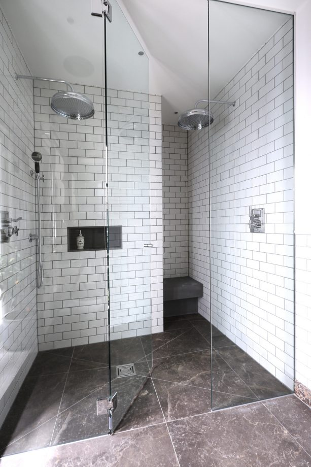 the combination between white subway tile with darker gray grout and natural gray stone flooring
