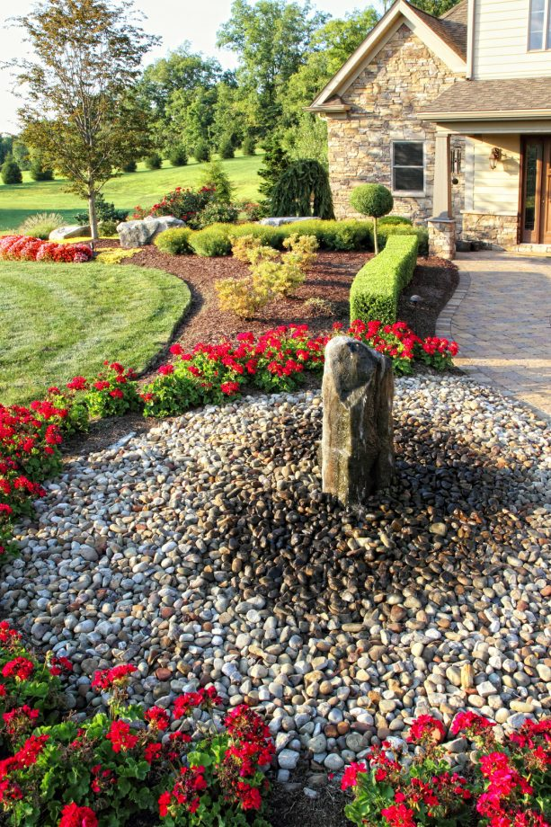 stone water fountain with rock mulch on the ground