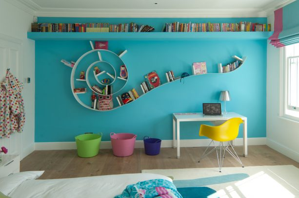 mustard yellow chair and a turquoise accent wall in a kid's bedroom