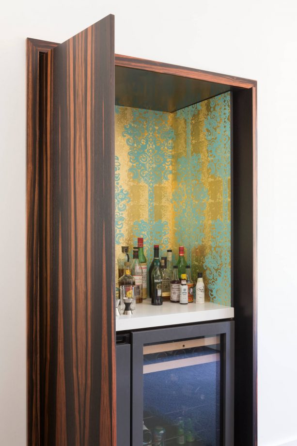 turquoise and gold wallpaper in a home bar design