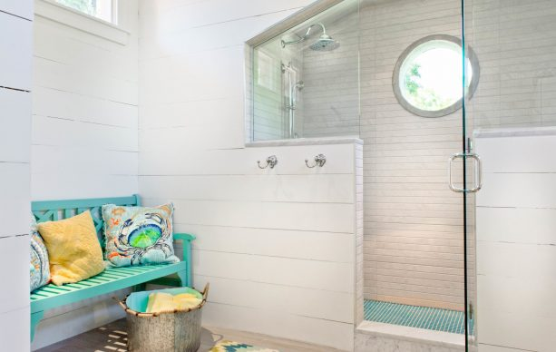 turquoise bench in a warm-white beach-style bathroom