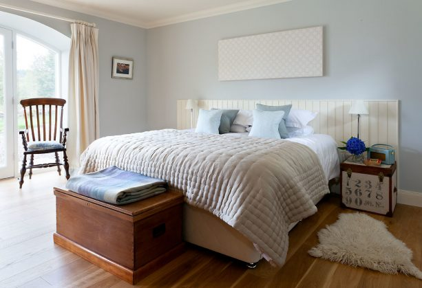 a rustic bedroom with soft blue accents, tan bed, and tan blanket