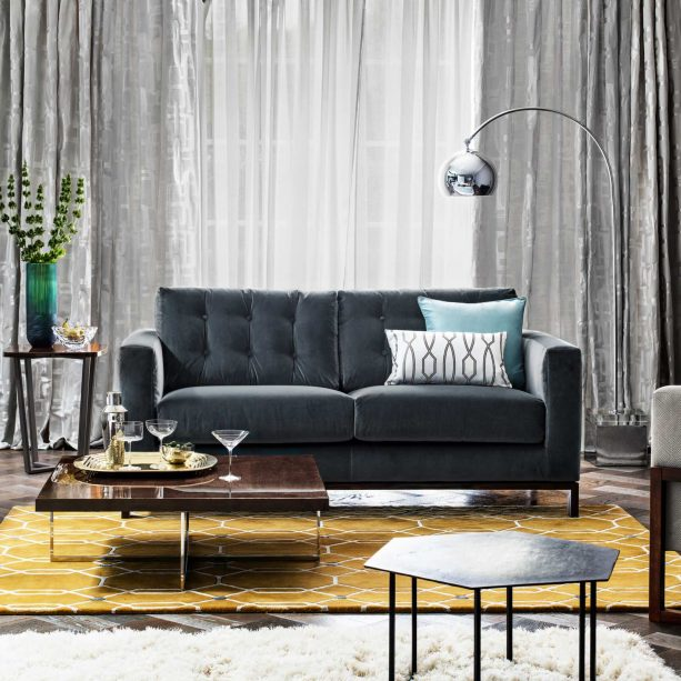 golden yellow area rug with white geometric details in a grey-dominated living room