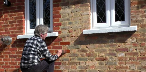 applying stain on old exterior brick wall by using brush