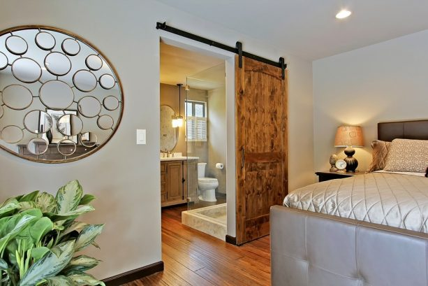 a bathroom barn door with industrial-style hardware and track