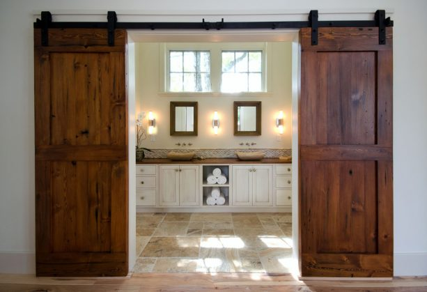a master bathroom behind double sliding barn door
