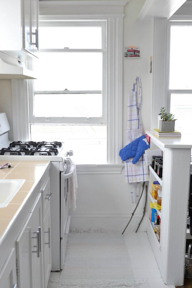 a half wall with built-in shelf in a small eclectic kitchen design