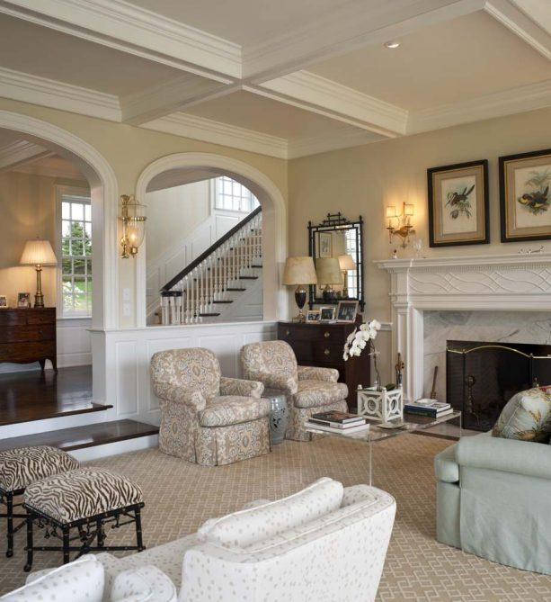 a half wall with columns separating the traditional living room and the hallway