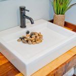 a white sink with yellow rocks covering the drain