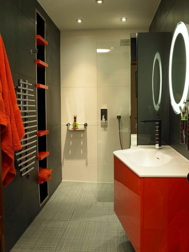 a contemporary bathroom with red and black color theme