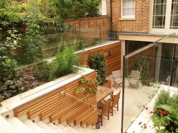 a sunken walkout basement patio with cedar trellis on each side