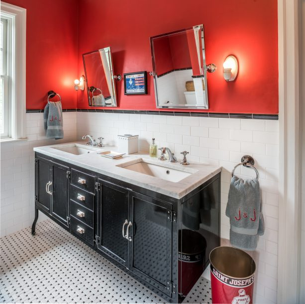an eclectic bathroom with glossy black double-sink vanity and red walls