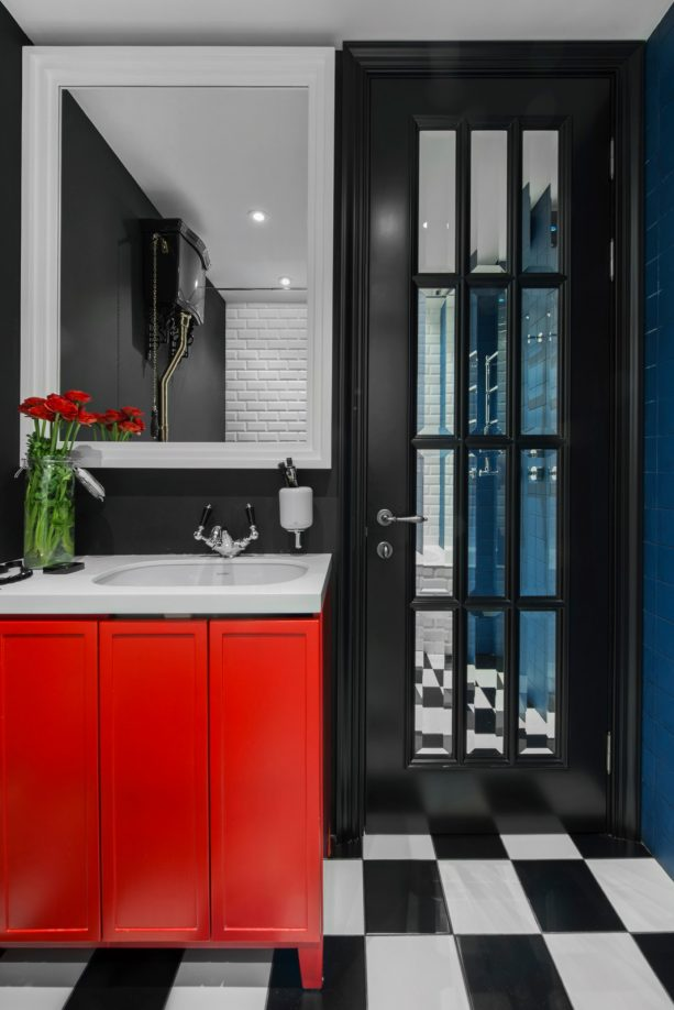 unique contemporary bathroom interior with black walls, black French door, and bright red vanity