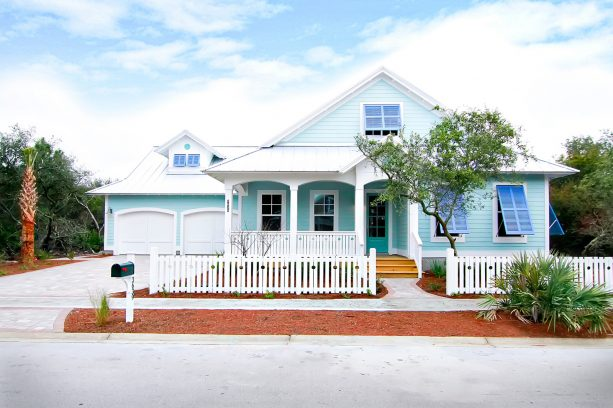 a beach-style house in light blue color with white roof
