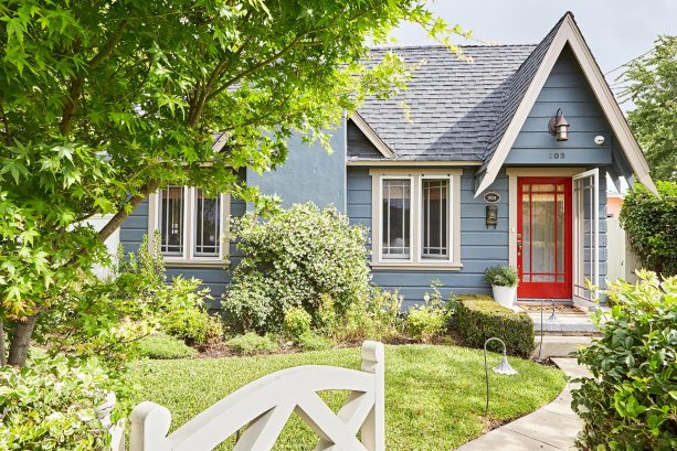 a cozy-looking Tudor cottage with stone blue wall siding, beige trim, and bright red front door