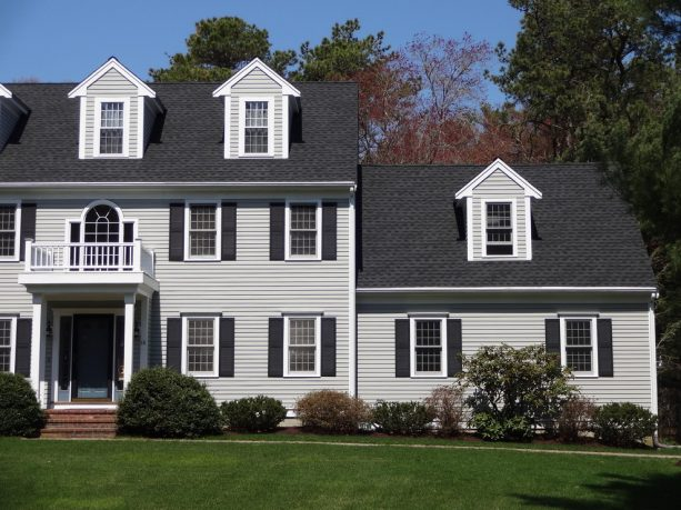 a light grey traditional home exterior with charcoal grey roof