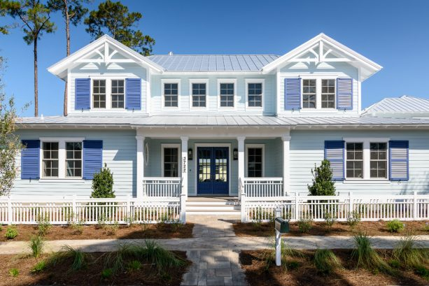 a beach style house with bright blue wall siding and Luxe Blue front door and shutters