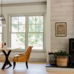 a farmhouse dining room with off-white walls, grey trim, and grey windows