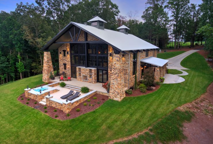 a lake house with multi-tones brick wall and white metal roof