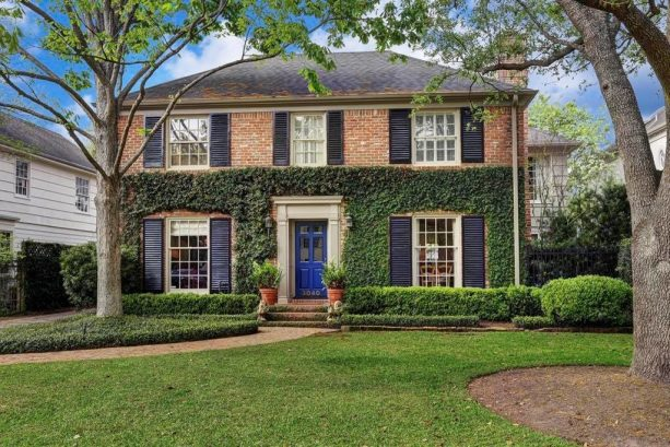 navy front door paired with black shutters in red brick home exterior